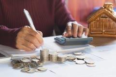 La mano de la mujer está presionando la calculadora con las monedas de la pila en el th Fotografía de archivo libre de regalías