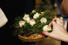 La mano de la mujer está tomando una pieza de un plato exótico durante una cena corporativa de lujo del acontecimiento imágenes de archivo libres de regalías