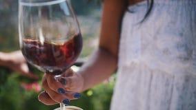 La mano de la mujer joven sacude el vidrio de vino rojo al aire libre almacen de video