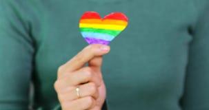 La mano de la mujer lleva a cabo forma del corazón del arco iris de la bandera de LGBT almacen de video