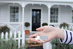 La mano de la mujer lleva a cabo una llave contra una casa en Auckland Nueva Zelanda Imagen de archivo libre de regalías