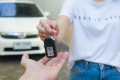 La mano de la mujer de negocios da la llave del coche foto de archivo libre de regalías