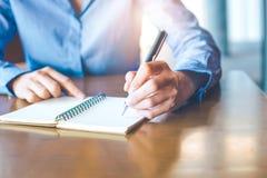 La mano de la mujer de negocios está escribiendo en la libreta con la pluma en oficina Imagen de archivo libre de regalías