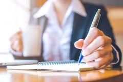 La mano de la mujer de negocios está escribiendo en la libreta con una pluma en oficina Foto de archivo