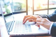 La mano de la mujer de negocios está funcionando en un ordenador portátil en una oficina Imagen de archivo libre de regalías