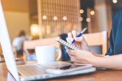 La mano de la mujer de negocios está funcionando en un ordenador portátil y un writin Fotografía de archivo libre de regalías