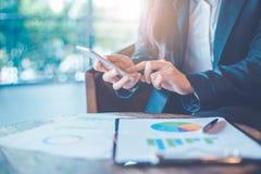 La mano de la mujer de negocios está utilizando smartphone y funciona en cartas y Imágenes de archivo libres de regalías