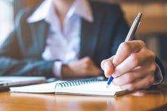 La mano de la mujer de negocios que trabaja en un ordenador portátil está escribiendo en n Fotos de archivo