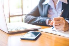 La mano de la mujer de negocios que trabaja en un ordenador portátil está escribiendo en n Imágenes de archivo libres de regalías