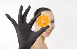 La mano de la mujer negra que lleva a cabo mitades anaranjadas cerca de su cara Mano negra con el mandarín sabroso brillante imagen de archivo