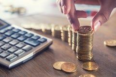 La mano de la mujer puso monedas euro con un efecto del crecimiento Todavía vida con cackulator del plan empresarial y moneda del foto de archivo libre de regalías