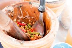La mano de la mujer que cocina la ensalada, la zanahoria y la hierba verdes picantes de la papaya en el mortero de madera, vended Fotos de archivo libres de regalías