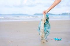 La mano de la mujer que cogía utilizó la bolsa de plástico en la playa de la arena, limpiando la playa de la playa Contaminación  imagen de archivo