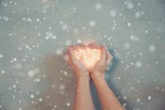 La mano de la mujer que hace la forma de un corazón, llevando a cabo luces de la Navidad calientes, fondo de madera, visión super imagen de archivo