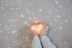 La mano de la mujer que hace la forma de un corazón, llevando a cabo luces de la Navidad calientes, fondo de madera, visión super fotografía de archivo libre de regalías