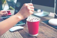 La mano de la mujer que mezcla el café mientras que trabaja en el mate de la tienda de café se aplica Foto de archivo libre de regalías