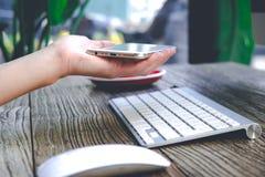 La mano de la mujer que sostiene el teléfono móvil elegante con el teclado y el ratón Imagen de archivo libre de regalías