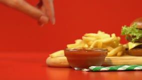 La mano de la mujer que sumerge las patatas fritas en la salsa de la salsa, alimentos de preparación rápida combinados, cierre pa almacen de metraje de vídeo