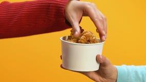 La mano de la mujer que toma el palillo graso ofrecido por la persona, problemas del colesterol, dieta almacen de video