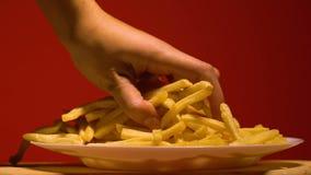 La mano de la mujer que toma las patatas fritas de la placa, apego de la comida basura, cámara lenta metrajes