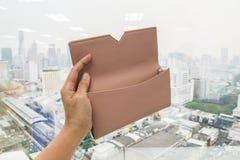 La mano de la mujer sostiene la cartera de cuero beige linda para el dinero con la mano izquierda Fotografía de archivo