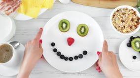 La mano de la mujer de la visión superior que torcía la placa con el smiley de risa de la fruta que gozaba del desayuno positivo  metrajes