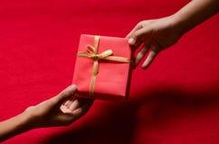 La mano de niños asiáticos tiene una caja de regalo de donante Fotografía de archivo