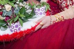 La mano de la novia en un vestido de Borgoña con un anillo de oro, un corazón, pulseras y cestas de flores Fotos de archivo