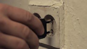 La mano de la persona pegó el cargador en el zócalo de potencia europea sucio almacen de metraje de vídeo