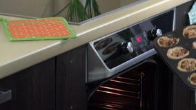 La mano de la presentadora con la puerta abierta protegida calor del horno del guante y toma las tortas con la carne metrajes