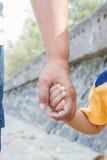 La mano de su hijo del padre control Foto de archivo libre de regalías
