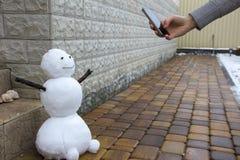 La mano de un adolescente sostiene el teléfono y toma una foto de un muñeco de nieve Imágenes de archivo libres de regalías