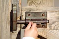 La mano de un bebé abre una puerta Foto de archivo libre de regalías