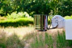 La mano de un camarero en un guante del blanco sostiene un envase en el aire abierto Foto de archivo libre de regalías