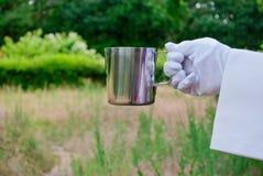 La mano de un camarero en un guante del blanco sostiene un pote del café en el aire abierto Fotos de archivo