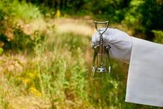 La mano de un camarero en un guante del blanco sostiene un sacacorchos del metal en el aire abierto Foto de archivo libre de regalías