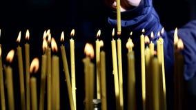 La mano de un cristiano enciende y pone una vela en Christian Church almacen de metraje de vídeo