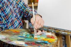 la mano de un hombre con un cepillo en la lona arte, creatividad, h foto de archivo