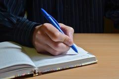 La mano de un hombre en una camisa azul escribe el texto con una pluma azul en un cuaderno en una tabla de madera en la igualació imagen de archivo