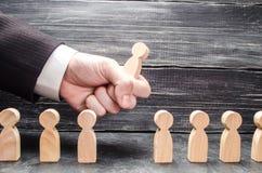 La mano de un hombre de negocios ase una figura de madera de un hombre de varios trabajadores El concepto de gestión de negocio imagen de archivo