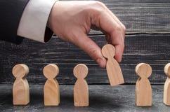la mano de un hombre de negocios toma una figura de madera de un hombre El concepto de trabajadores de la búsqueda, del alquiler  fotos de archivo