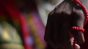 La mano de un hombre negro toca el rosario rojo metrajes