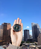 La mano de un hombre que lleva a cabo un compás magnético sobre edificios de una ciudad Imagen de archivo libre de regalías