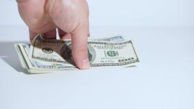 La mano de un hombre toma los dólares americanos de la tabla Fondo blanco Primer metrajes
