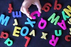 La mano de un pequeño niño aprende el alfabeto de la lengua inglesa imagenes de archivo