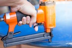 La mano de un trabajador está utilizando un arma del clavo imágenes de archivo libres de regalías