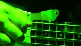 La mano de una bajo-guitarra de los juegos del hombre almacen de metraje de vídeo
