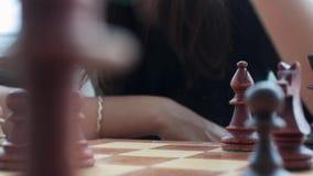 La mano de una chica joven hace un movimiento con un pedazo de ajedrez sobre el tablero de ajedrez en el cuarto Jugar a ajedrez,  almacen de video