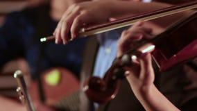 La mano de una muchacha que toca el violín El arco se mueve a lo largo de las secuencias que extraen música
