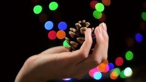 La mano de una muchacha sostiene un cono de abeto en fondo del bokeh, durante los días de fiesta de la Navidad en la cámara lenta almacen de metraje de vídeo